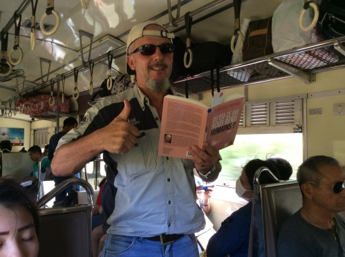 Dr Patrick Martiny reading the book on a train in Thailand