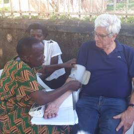 A retired nurse in the older persons' group in Bukonga taking JL's BP. It is normal, thank you!